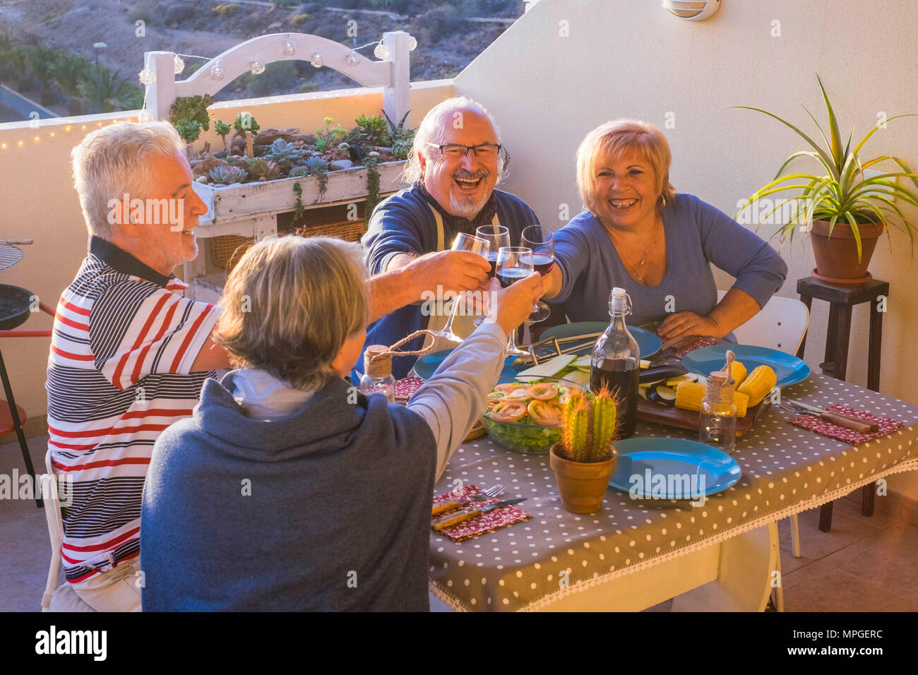 adult group of people having nice dinner outdoor in the terrace. enjoy the friendship with time together drinking and celebrating holiday or retired c - Stock Image