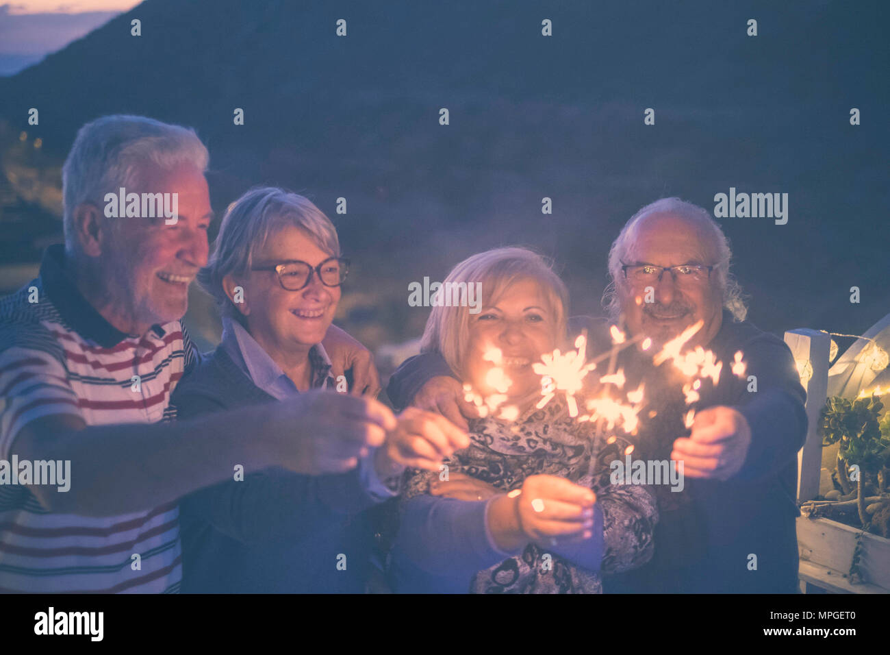 celebrate event new year eve at midnight for group of nice people beautiful senior adult. men and women with sparkles outdoor by night - Stock Image