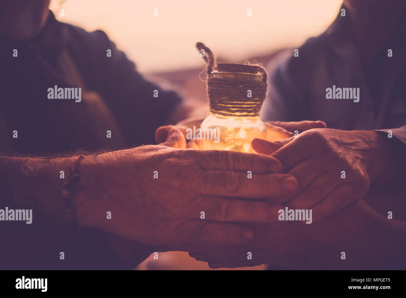8 joined hands hold a small glass jar containing a yellow light. Stock Photo