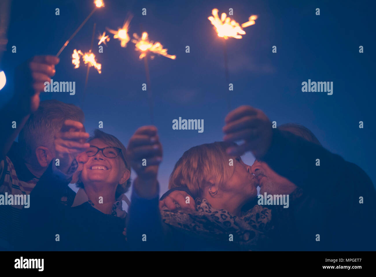 celebration party for holiday night or new year eve 2019. group of aged men and women people with fire sparks. everybody kissing and having a lot of f - Stock Image