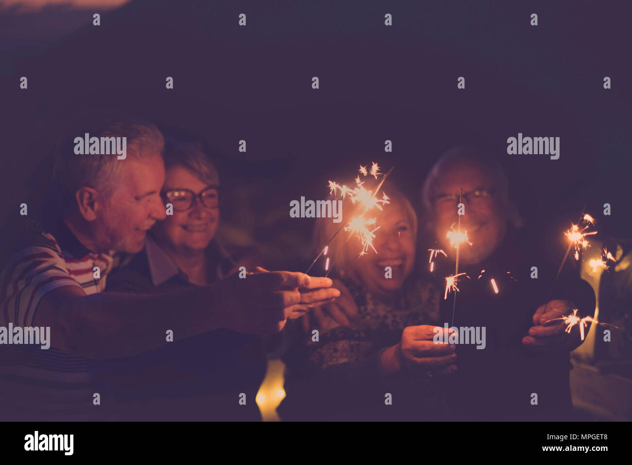 celebration time for party or new year eve for a group of senior friends with fire sparks. averybody together having  fun at night smiling and laughin - Stock Image