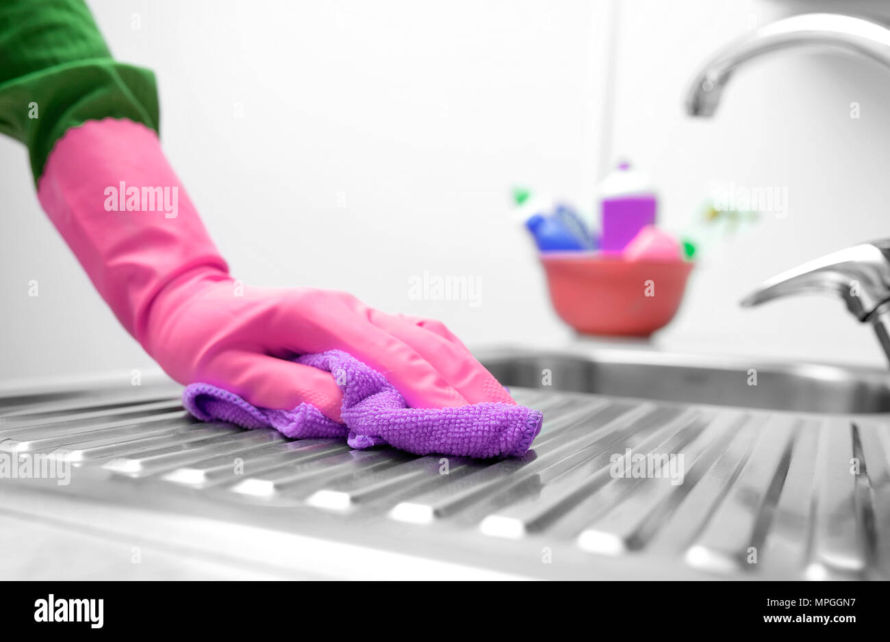 Hand in a rubber glove washes the sink. - Stock Image