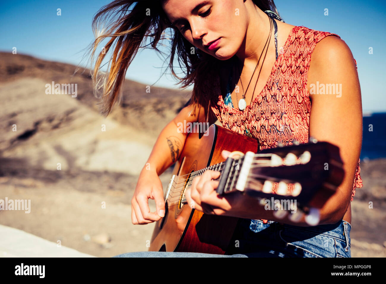 nice caucasian blonde girl playing guitar outdoor in tenerife. frredom and hippy vacation concept. beautiful face doing music. - Stock Image