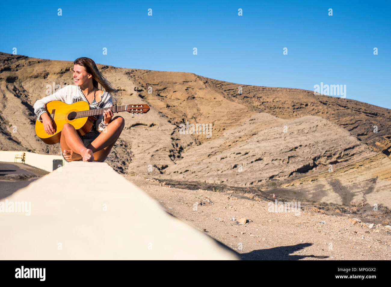 nippy and alternative lifestyle concept for blonde caucasian model smiling outdoor with mountains on the background and playing an old acoustic guitar - Stock Image