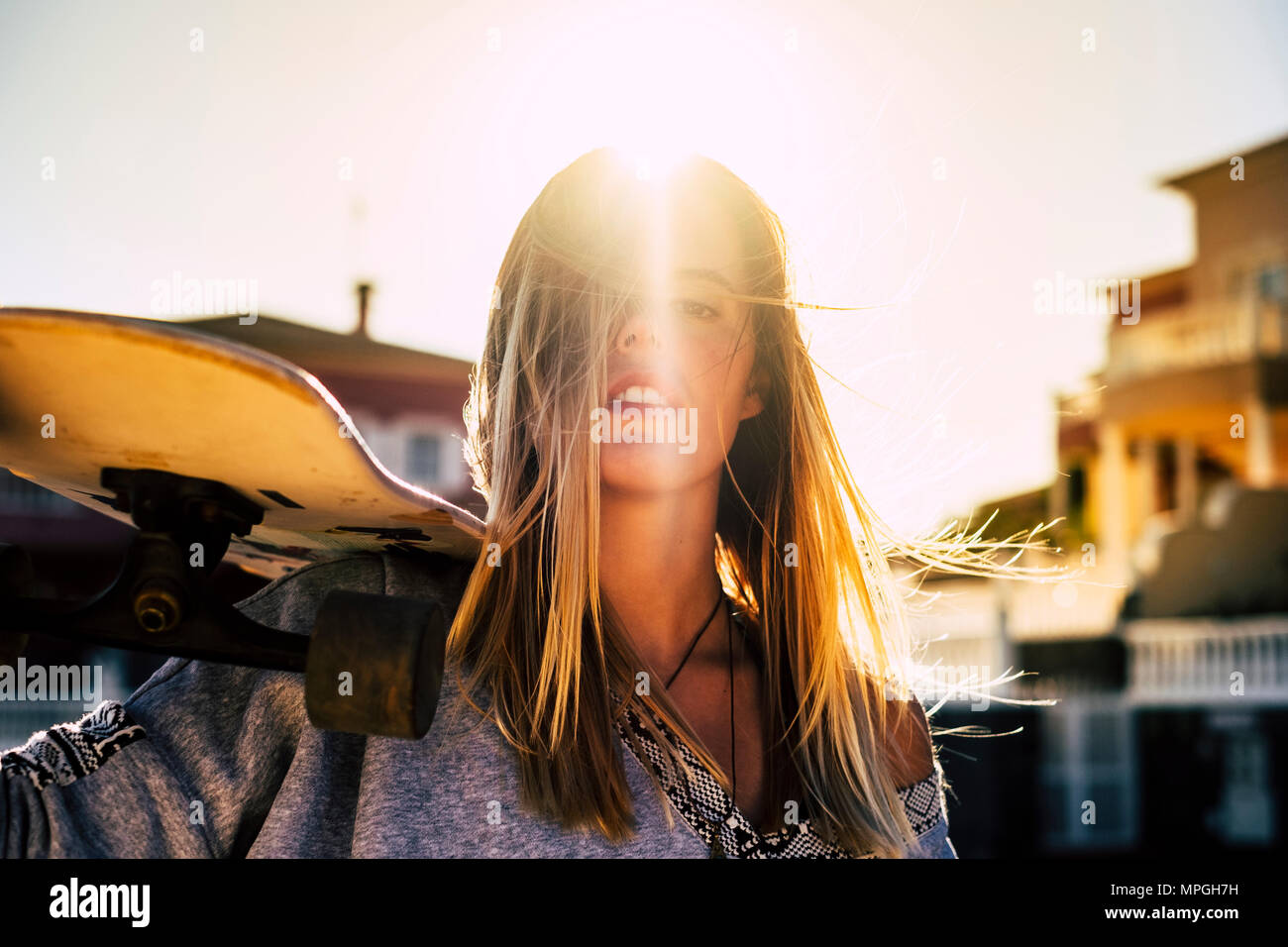 nice portrait for a beautiful long blonde hair young woman with her skateboard on the shoulder. rebel and sunny day of vacation concept. travel and en - Stock Image