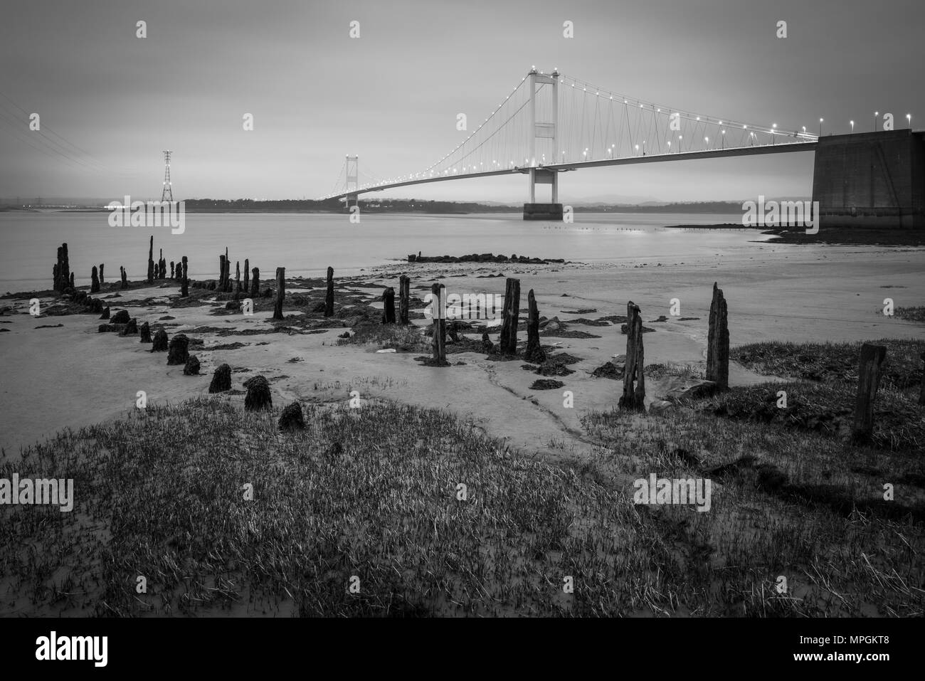 The Severn Bridge over the River Severn between England and Wales from the beach at Aust, Gloucestershire. - Stock Image