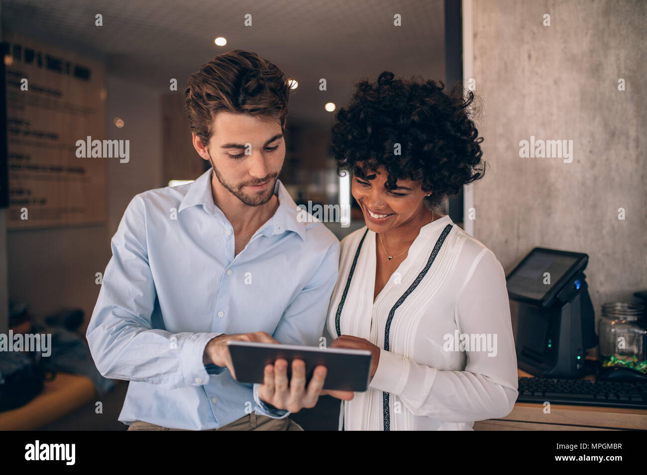 Two restaurant business partners standing together and looking at digital tablet. Man and woman using digital tablet in a cafe. Stock Photo
