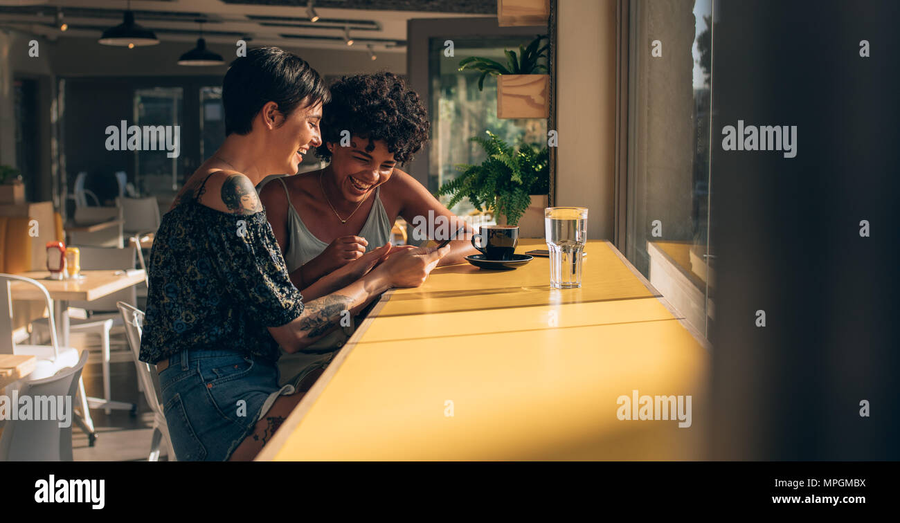 Two women sitting at cafe engrossed in using a smart phone. Female friends looking at mobile phone and smiling. - Stock Image
