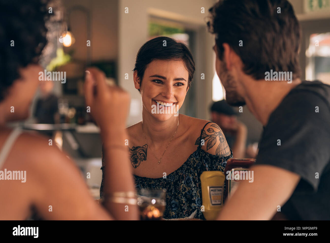 Beautiful young woman smiling and talking with her friends at a coffee. Group of young people meeting at restaurant. - Stock Image