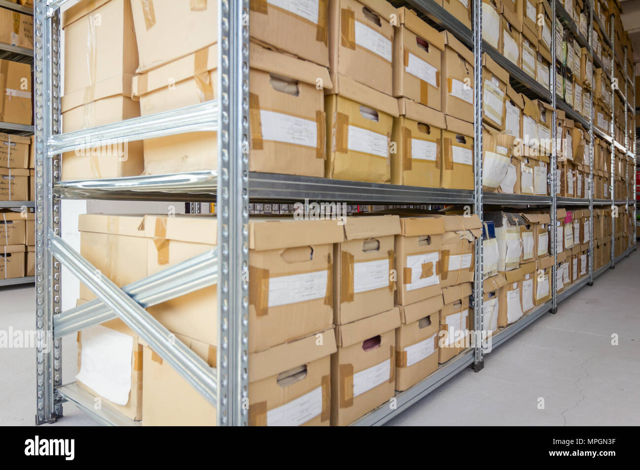 Stacks of files and paperwork placed in bookshelves with folders and documents in cardboard box archive, storage room. - Stock Image