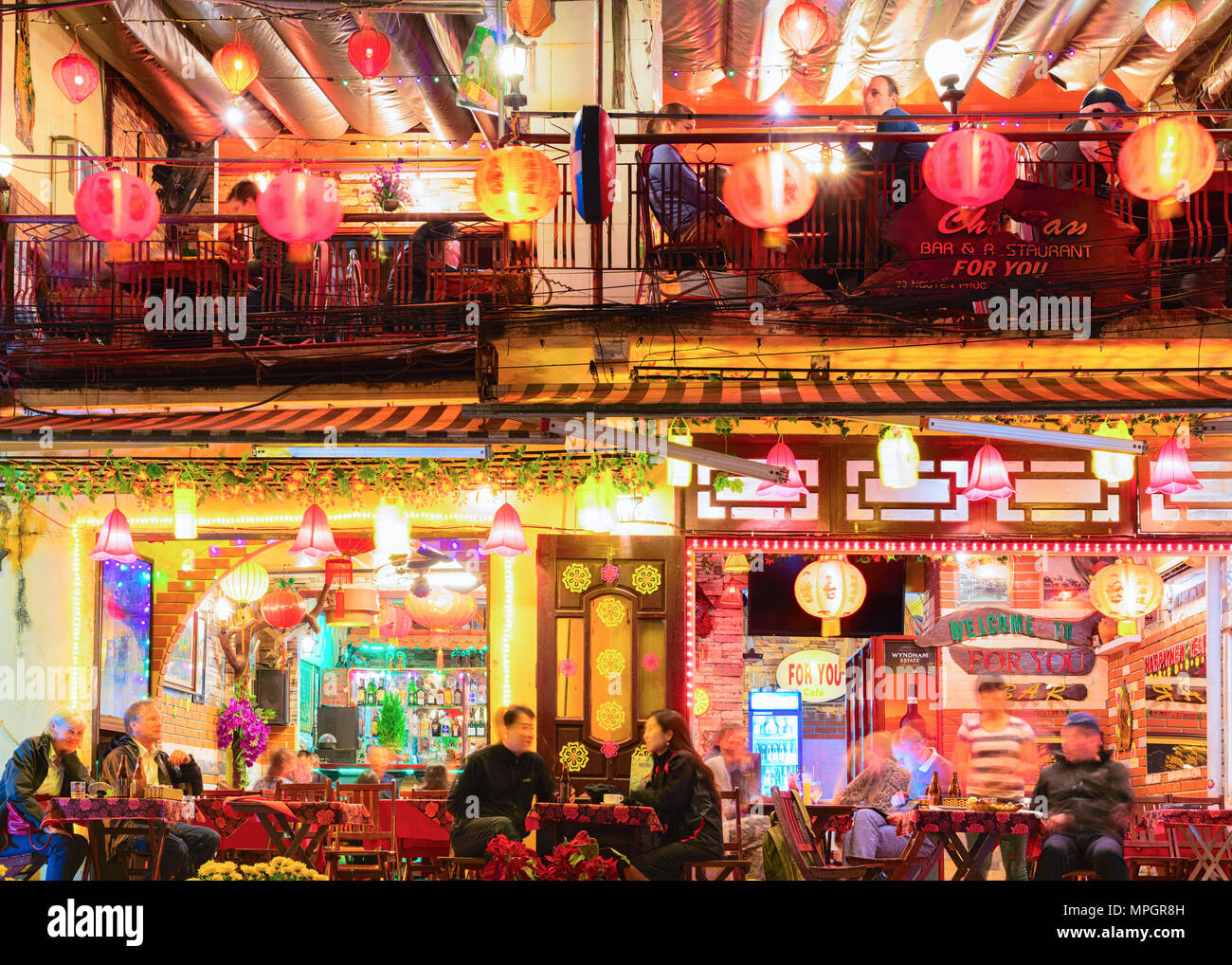 Hoi An, Vietnam - February 17, 2016: People at the street restaurant in Hoi An, Vietnam. Late in the evening Stock Photo