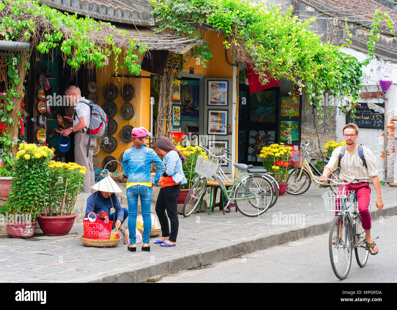 Hoi An, Vietnam - February 17, 2016: Man on bicycle at the street of old city of Hoi An, Vietnam Stock Photo