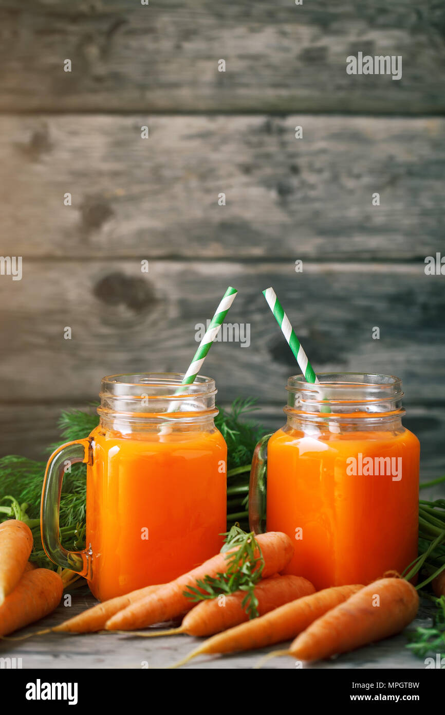 Fresh Carrot and carrot juice on Wooden Table in Garden. Vegetables Vitamins Keratin. Natural Organic Carrot lies on Wooden background. - Stock Image