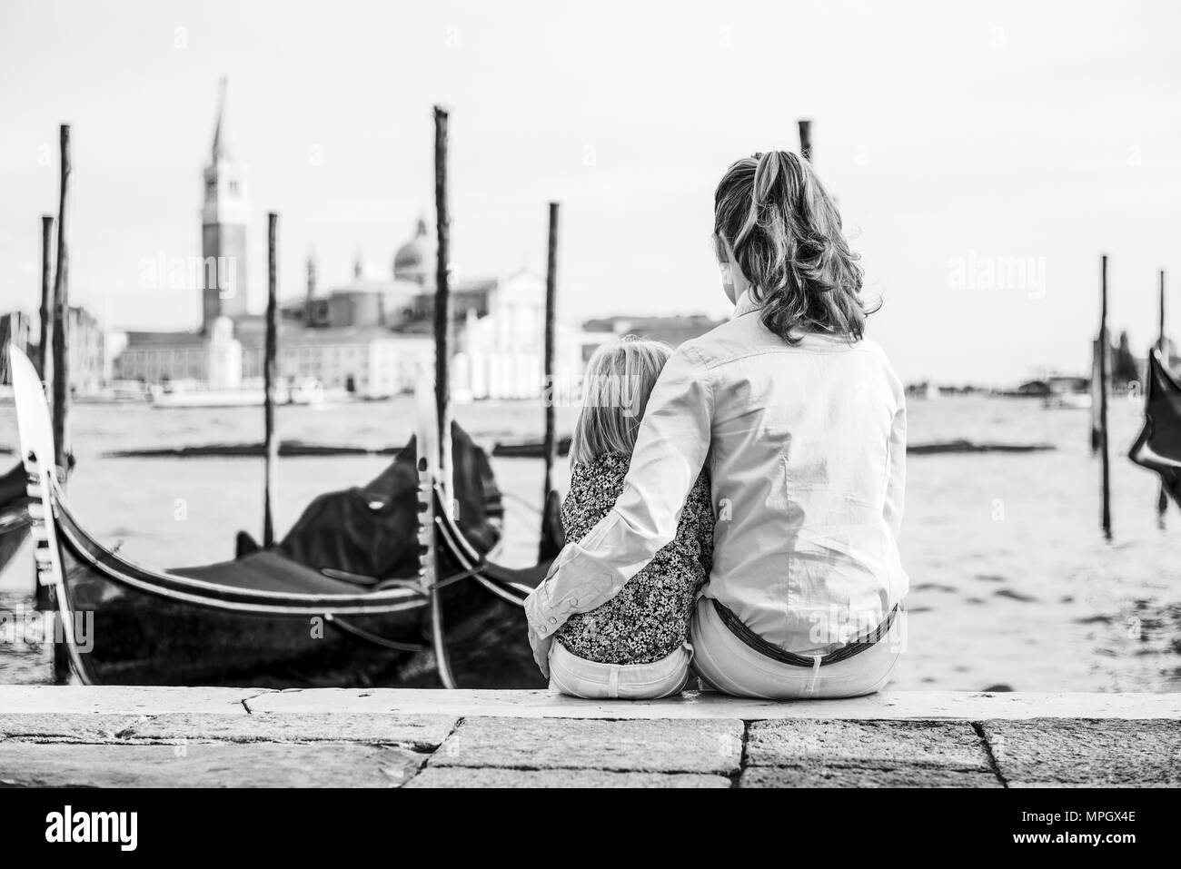 Portrait of mother and baby sitting on grand canal embankment in venice, italy. rear view - Stock Image
