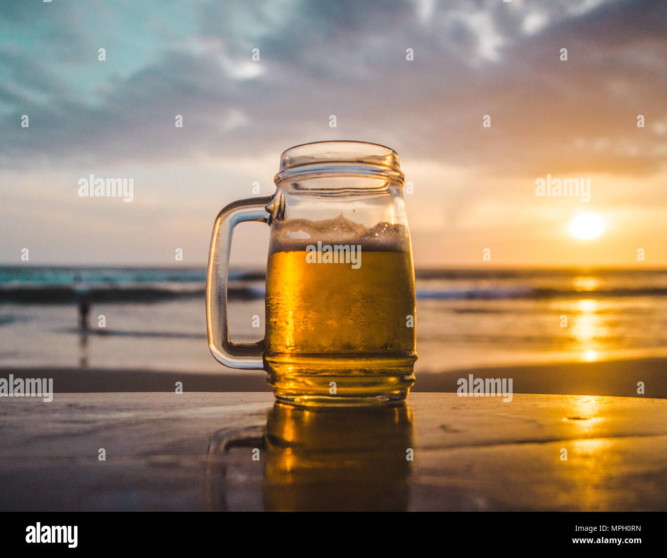 Glass jar of beer on a wooden table looking out at the ocean during sunset - Stock Image