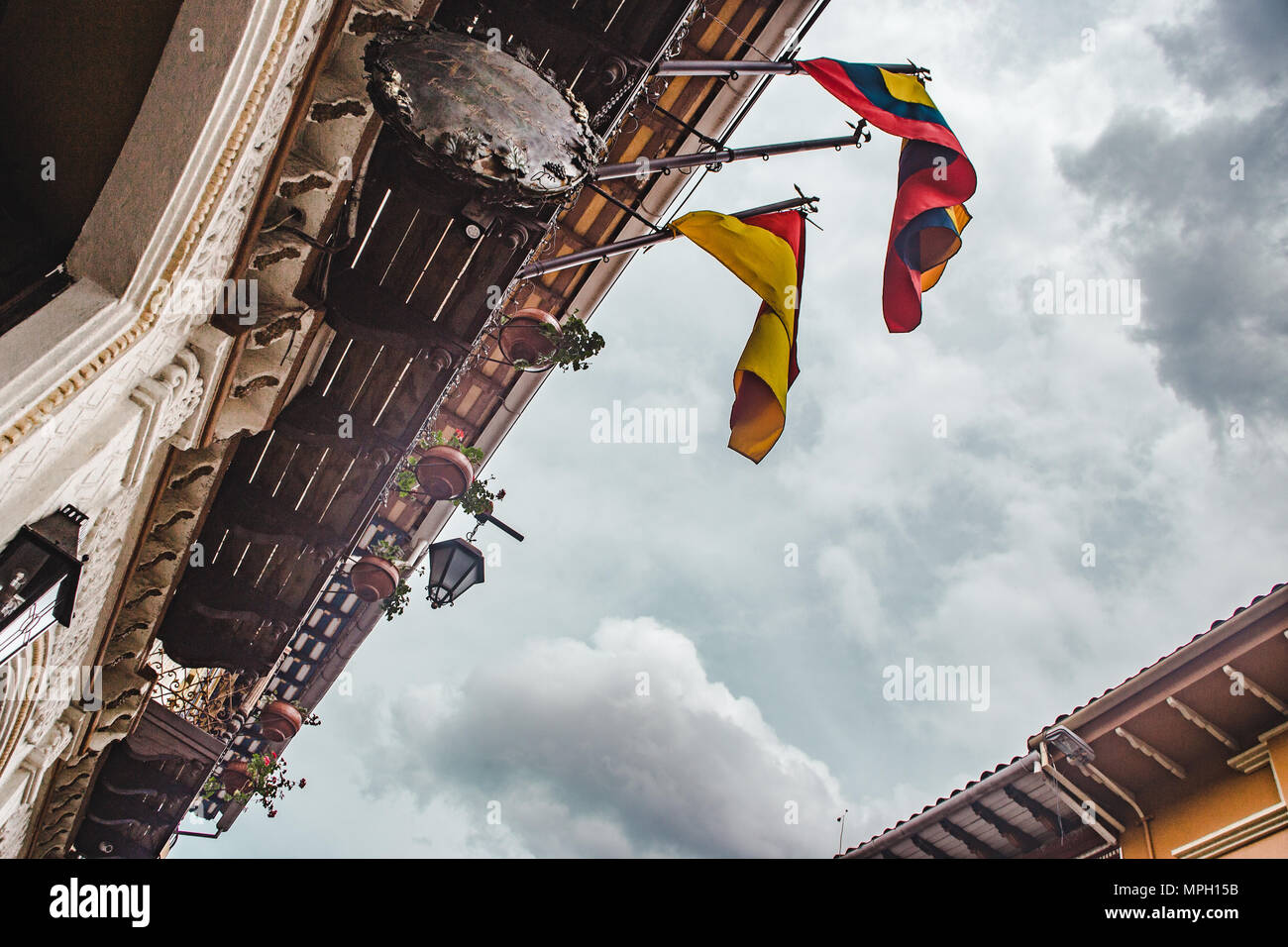 Upwards view of Ecuadorian flags hanging from a colonial building in Cuenca, Ecuador - Stock Image