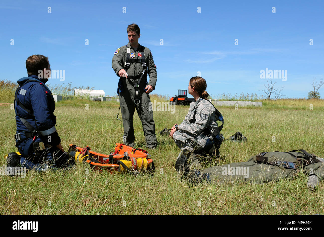 Rescue Crewman Kurt Pride, Royal Australian Air Force Base Tindal helicopter unit member, U.S. Air Force Capt. Paul Ward, 90th Fighter Squadron Flight Doctor, and Tech. Sgt. Layla Dispense, 90th FS Independent Duty Medical Technician, prepare a dummy for transport on a stretcher during helicopter rescue training at RAAF Base Tindal, Feb. 28, 2017. Ward and Dispense are deployed to Australia as part of the Enhanced Air Cooperation, a joint training and exercise initiative under the Force Posture Agreement between the U.S. and Australian governments. (U.S. Air Force photo by Staff Sgt. Alexander - Stock Image