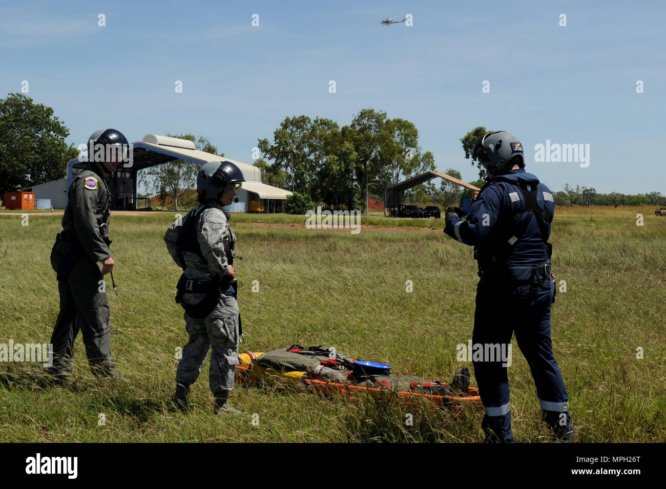 Rescue Crewman Kurt Pride (right), Royal Australian Air Force Base Tindal helicopter unit member, U.S. Air Force Capt. Paul Ward, 90th Fighter Squadron Flight Doctor, and Tech. Sgt. Layla Dispense, 90th FS Independent Duty Medical Technician, prepare a dummy for transport on a stretcher during helicopter rescue training at RAAF Base Tindal, Feb. 28, 2017. Ward and Dispense are deployed to Australia as part of the Enhanced Air Cooperation, a joint training and exercise initiative under the Force Posture Agreement between the U.S. and Australian governments. (U.S. Air Force photo by Staff Sgt. A - Stock Image