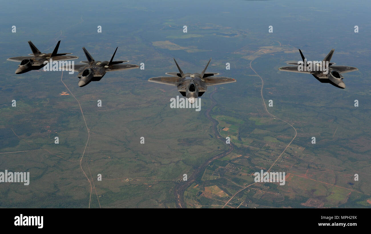 Four U.S. Air Force F-22 Raptors assigned to the 90th Fighter Squadron fly in formation in the skies above Royal Australian Air Force Base Tindal, Australia, March 2, 2017. Twelve F-22 Raptors and approximately 200 U.S. Air Force Airmen participated in the first Enhanced Air Cooperation, an initiative under the Force Posture Agreement between the U.S. and Australia. (U.S. Air Force photo by Staff Sgt. Alexander Martinez) - Stock Image