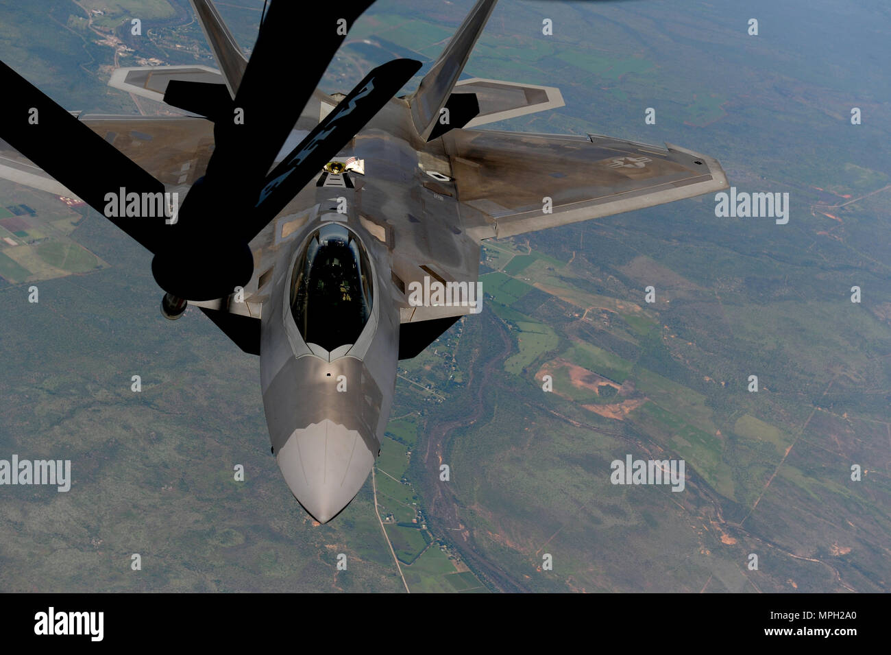 A U.S. Air Force F-22 Raptor assigned to the 90th Fighter Squadron approaches a U.S. Air Force KC-135 Stratotanker in order to receive fuel in the skies above Royal Australian Air Force Base Tindal, Australia, March 2, 2017. Twelve F-22 Raptors and approximately 200 U.S. Air Force Airmen participated in the first Enhanced Air Cooperation, an initiative under the Force Posture Agreement between the U.S. and Australia. (U.S. Air Force photo by Staff Sgt. Alexander Martinez) - Stock Image