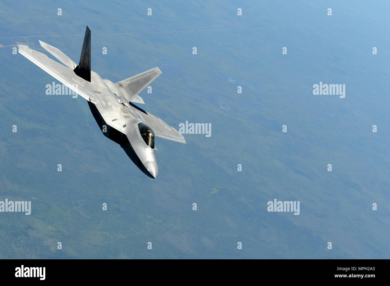A U.S. Air Force F-22 Raptor flies above Royal Australian Air Force Base Tindal, Australia, March 2, 2017. Twelve F-22 Raptors and approximately 200 U.S. Air Force Airmen participated in the first Enhanced Air Cooperation, an initiative under the Force Posture Agreement between the U.S. and Australia. (U.S. Air Force photo by Staff Sgt. Alexander Martinez) - Stock Image