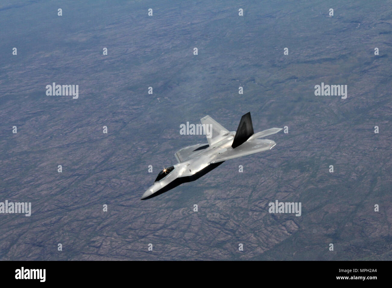 A U.S. Air Force F-22 Raptor flies above Royal Australian Air Force Base Tindal, Australia, March 2, 2017. Twelve F-22 Raptors and approximately 200 U.S. Air Force Airmen participated in the first Enhanced Air Cooperation, an initiative under the Force Posture Agreement between the U.S. and Australia. (U.S. Air Force photo by Maj. Lori Hodge) - Stock Image