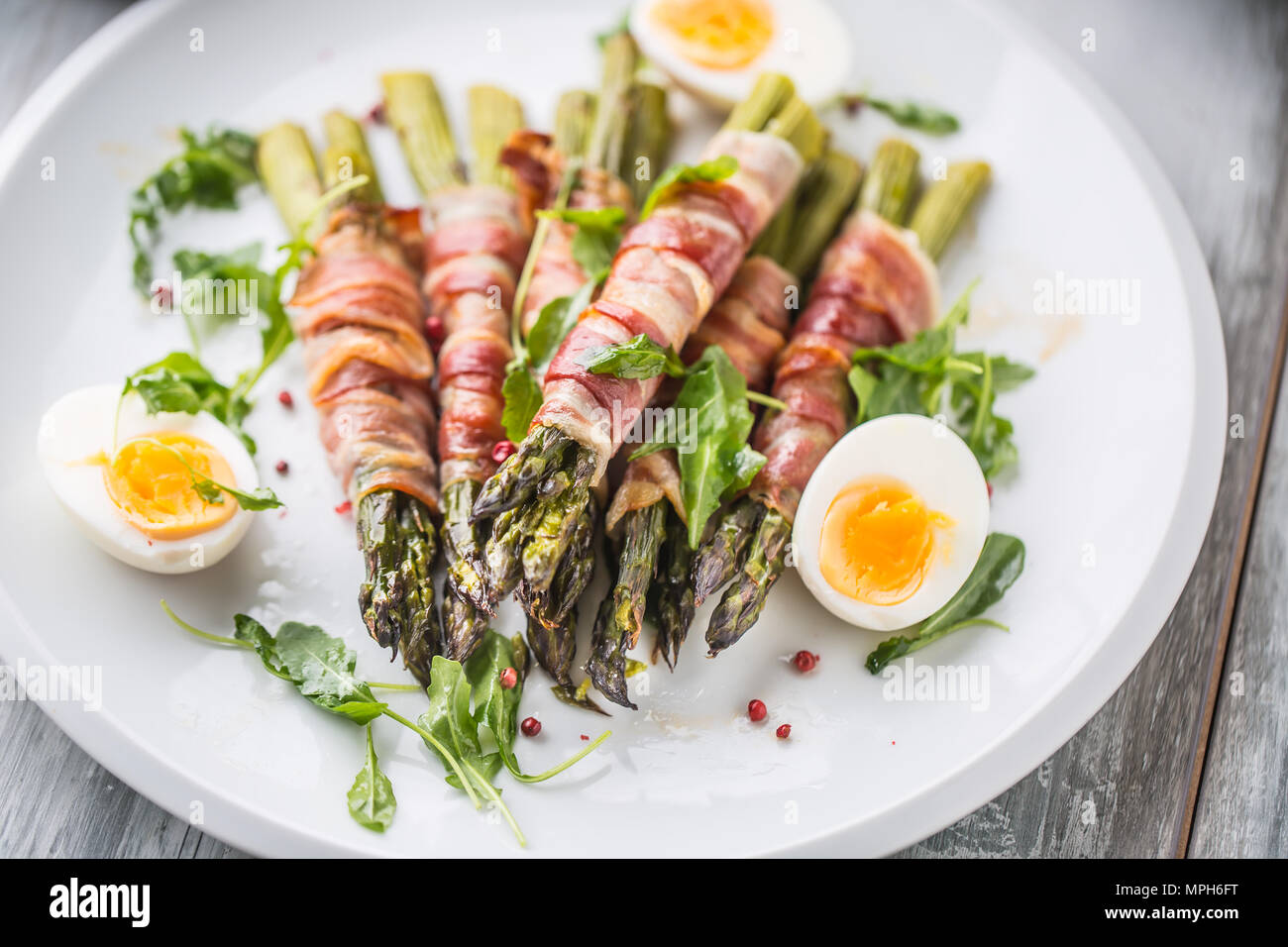 Fresh asparagus wrapped in bacon  on a white plate with arugula tomatoes and eggs. Stock Photo