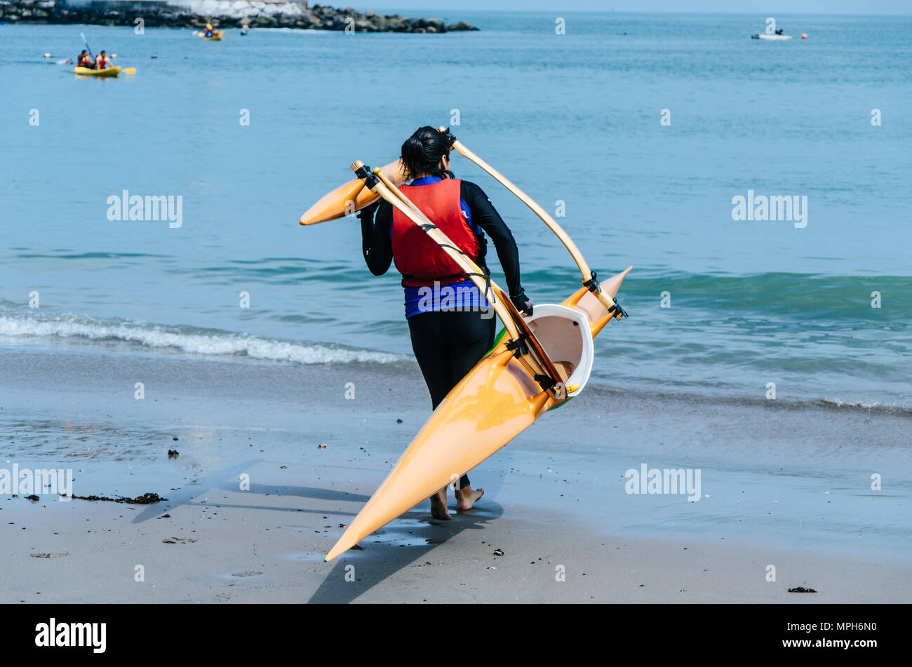 Young woman paddler transporting a canoe - Stock Image