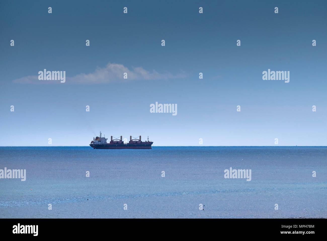 A cargo ship anchored in the sea. - Stock Image