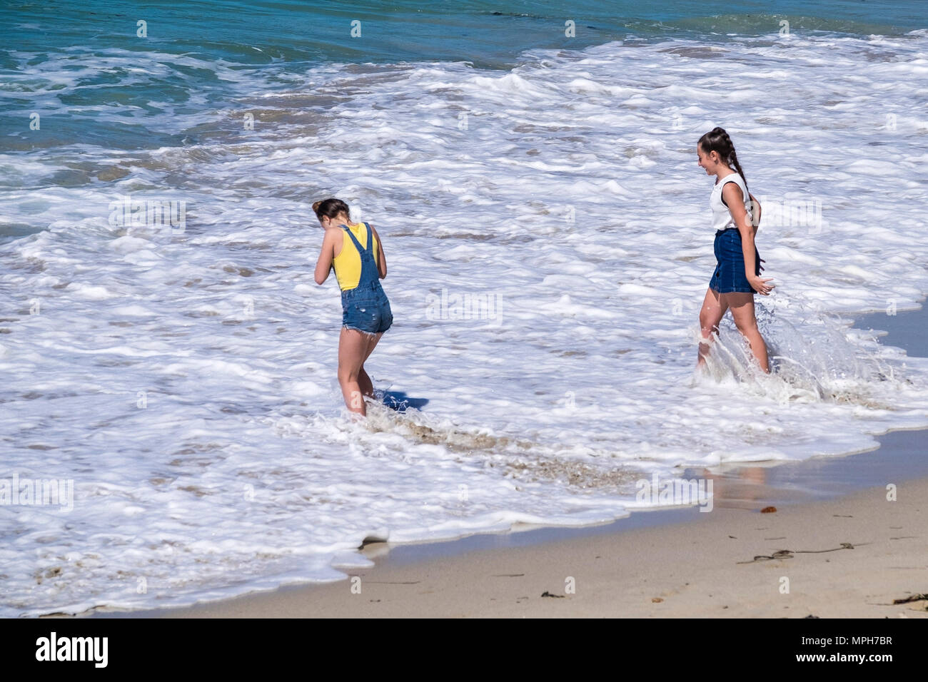 Young teenage girls paddling in the sea at Sennen Cove in Cornwall. - Stock Image