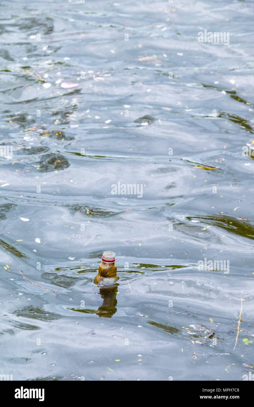 A plastic bottle floating on water. - Stock Image