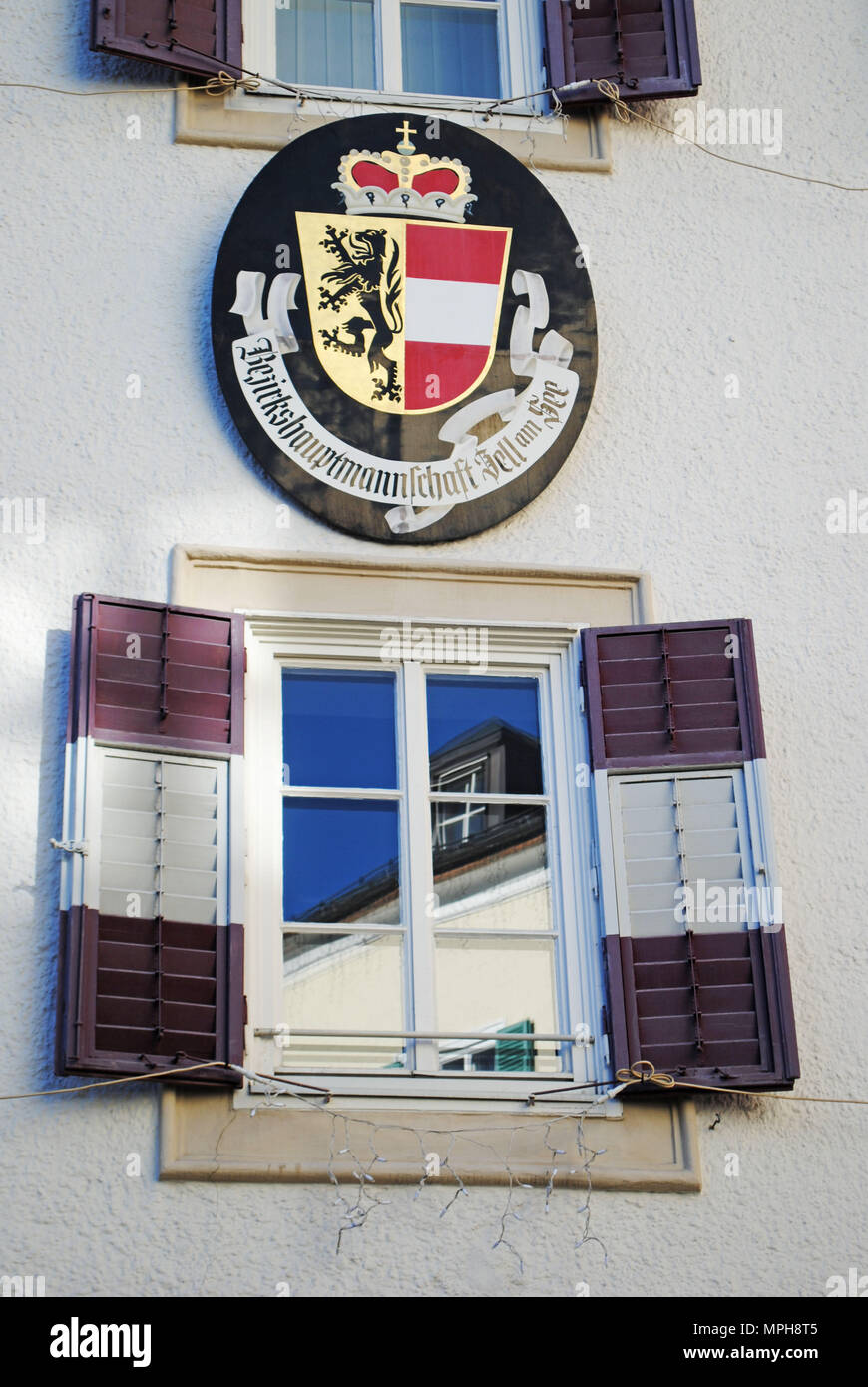 A detail on the district administration building in Zell am See, Austria, including the coat of arms and a window with wooden shutters. Stock Photo