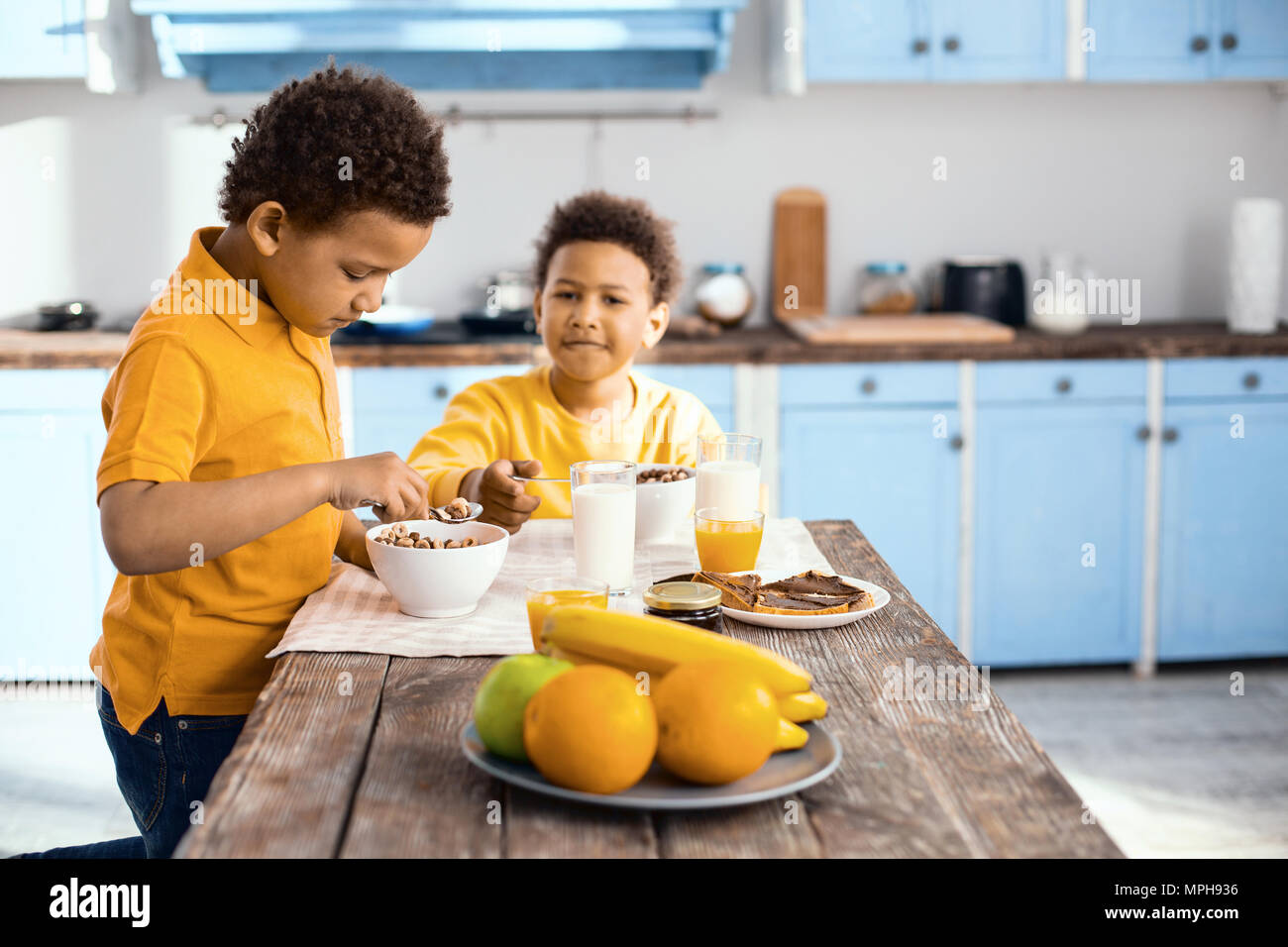 Pleasant little boys eating cereals for breakfast Stock Photo