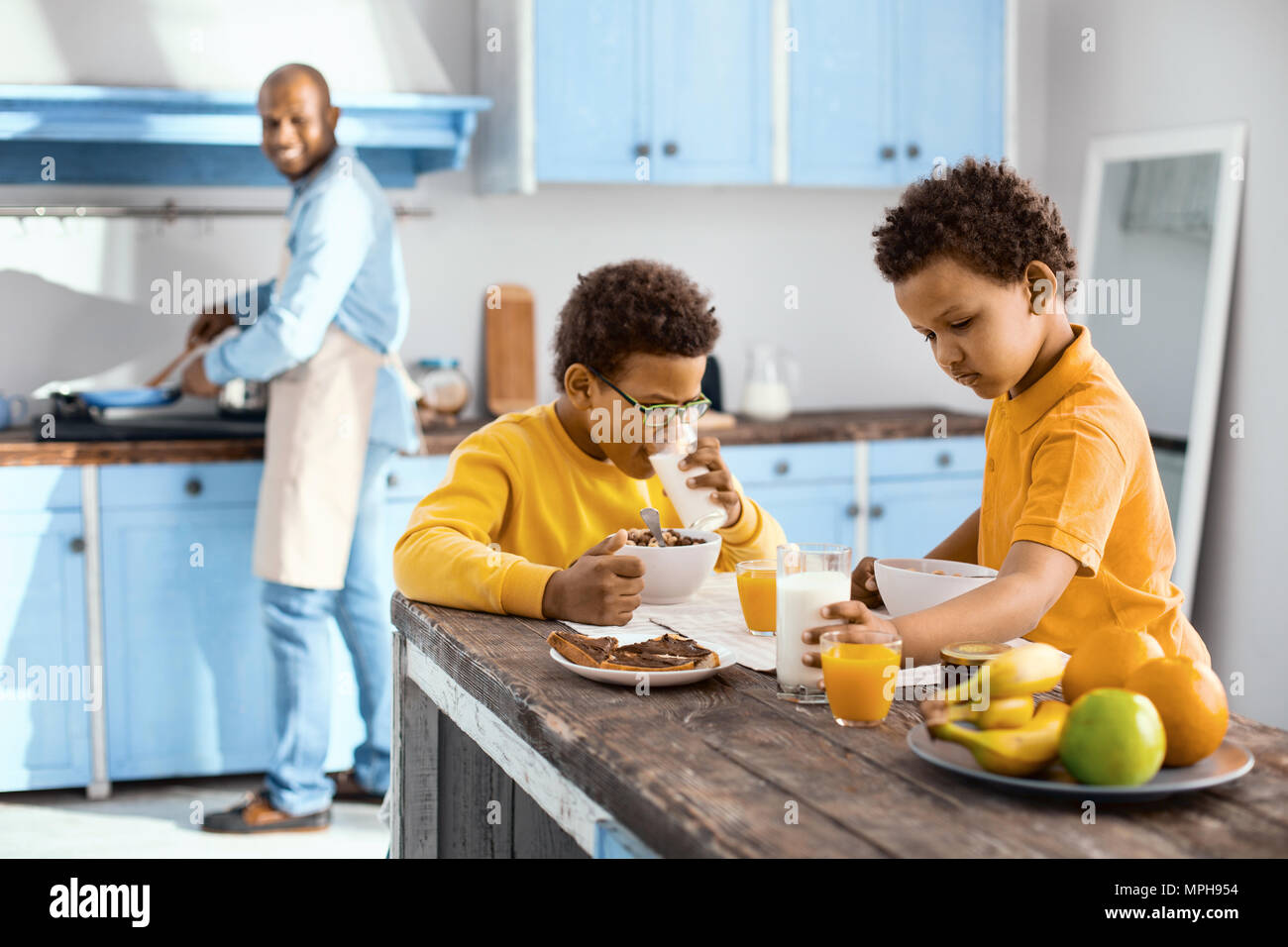 Pleasant children eating breakfast while their father cooking - Stock Image