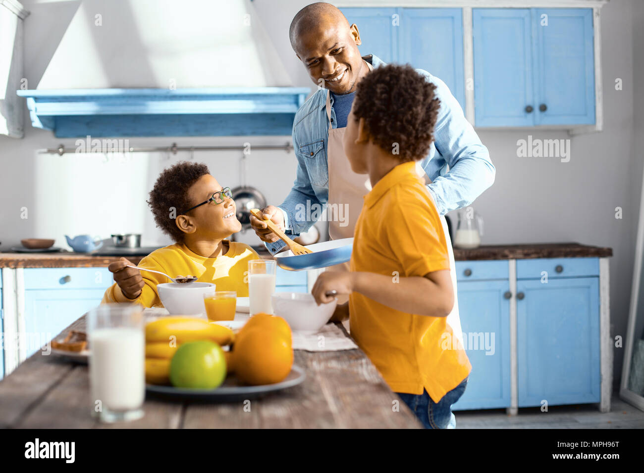 Cheerful young man offering another dish to his sons Stock Photo