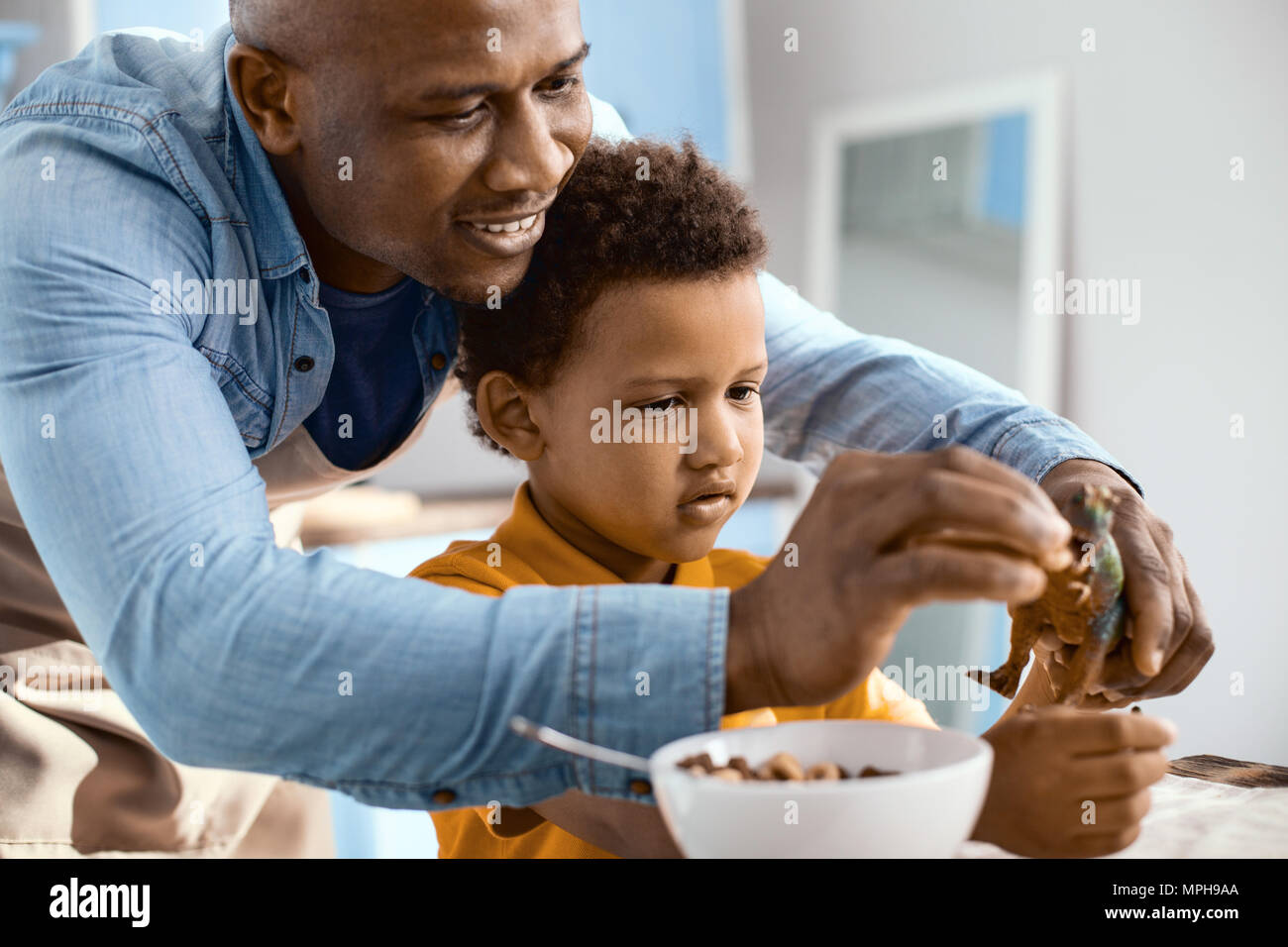 Happy young father feeding his sons toy dinosaur Stock Photo