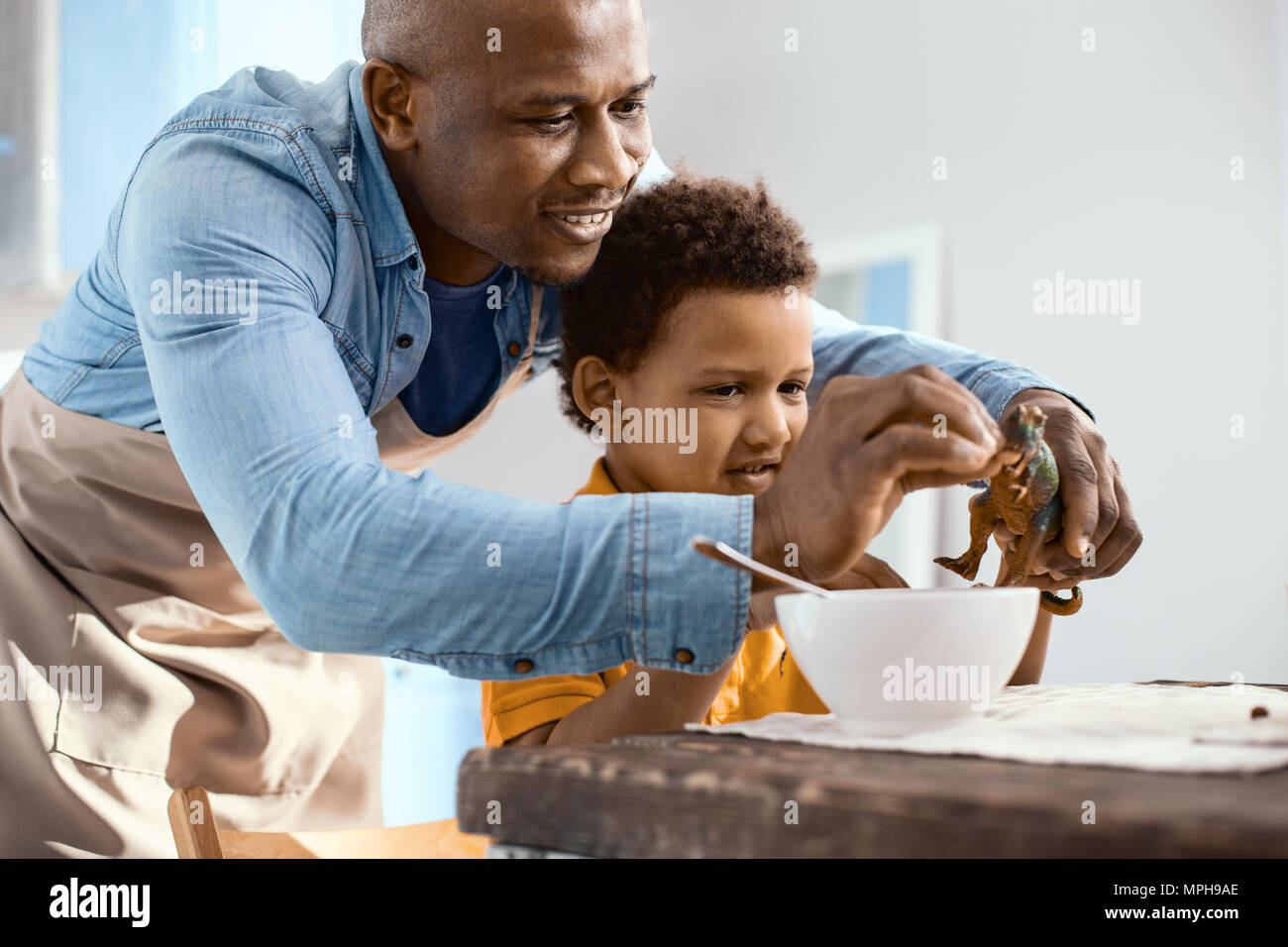 Caring father feeding cereals to his sons toy dinosaur Stock Photo