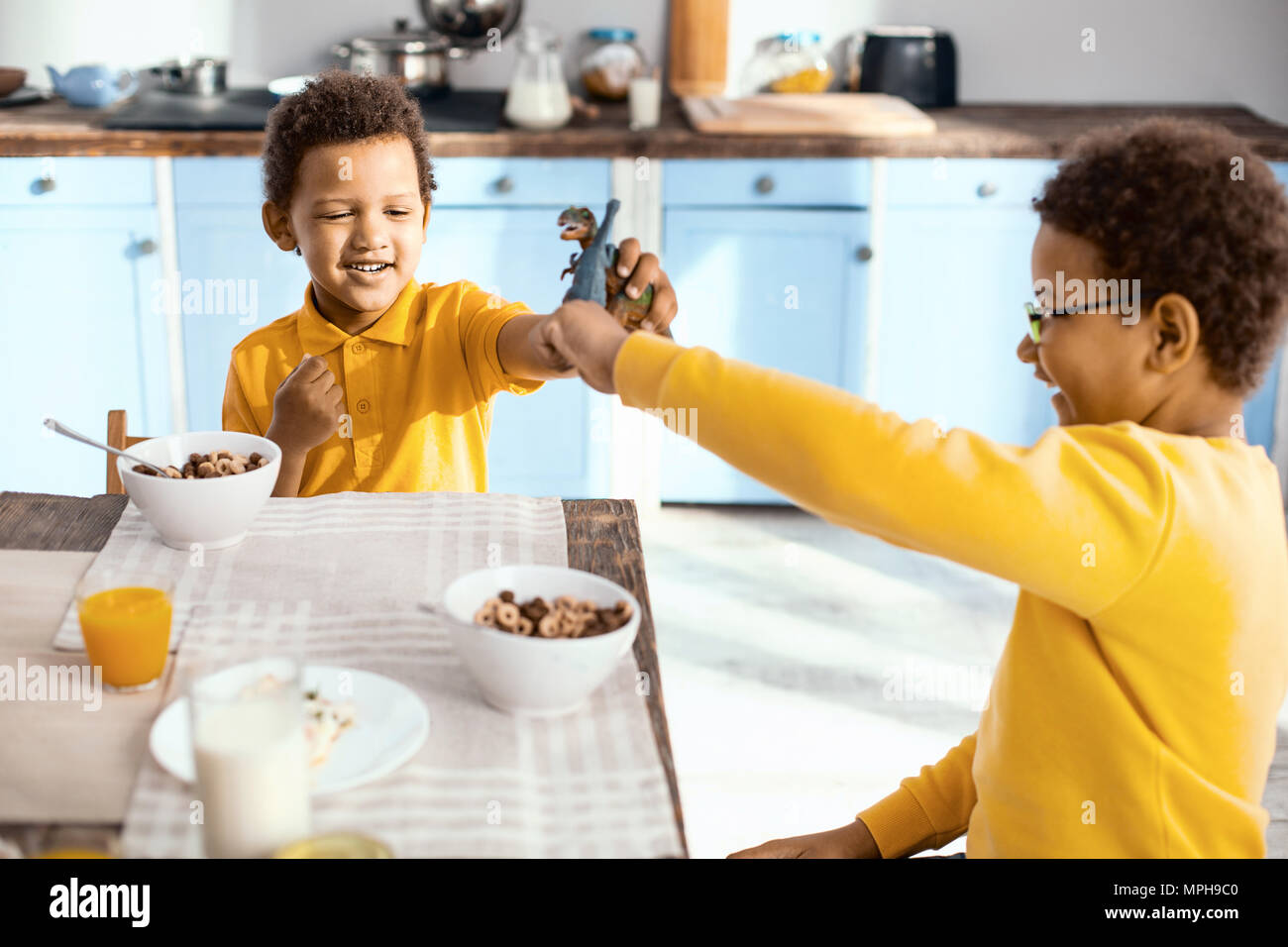 Cheerful little boys fighting with toy dinosaurs - Stock Image
