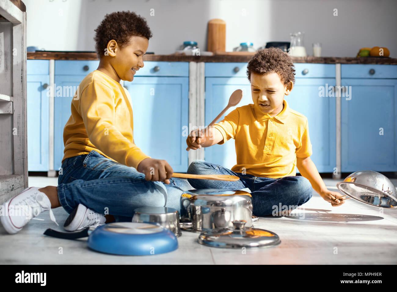Joyful little boys pretending to be musicians Stock Photo