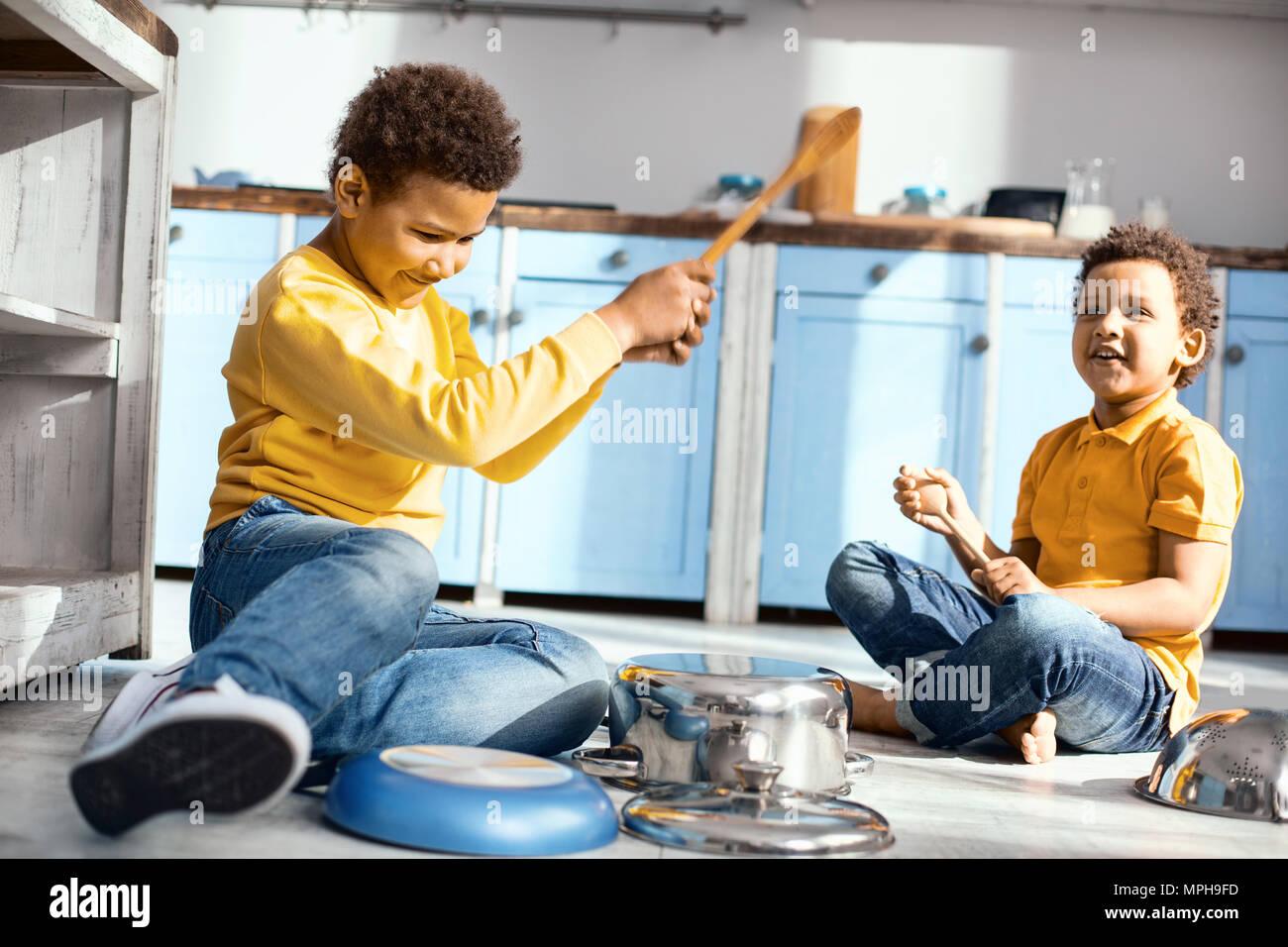 Pleasant little boys playing music on saucepans Stock Photo