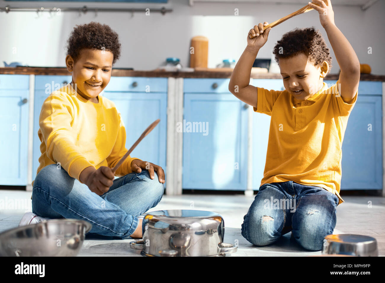 Cute little boys creating noise by drumming on saucepans Stock Photo
