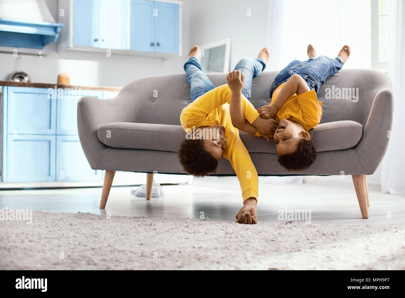 Upbeat little brothers lying on the couch and tickling each other Stock Photo