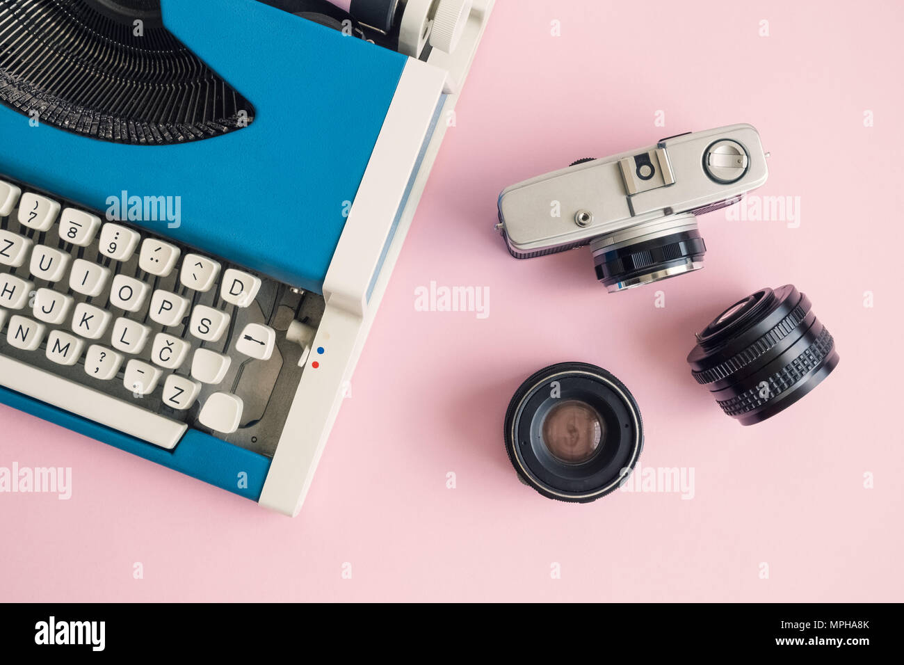 Flat Lay Of Blue Typewriter And Retro Camera With Lenses On Pastel Pink  Background Minimal Creative Concept.