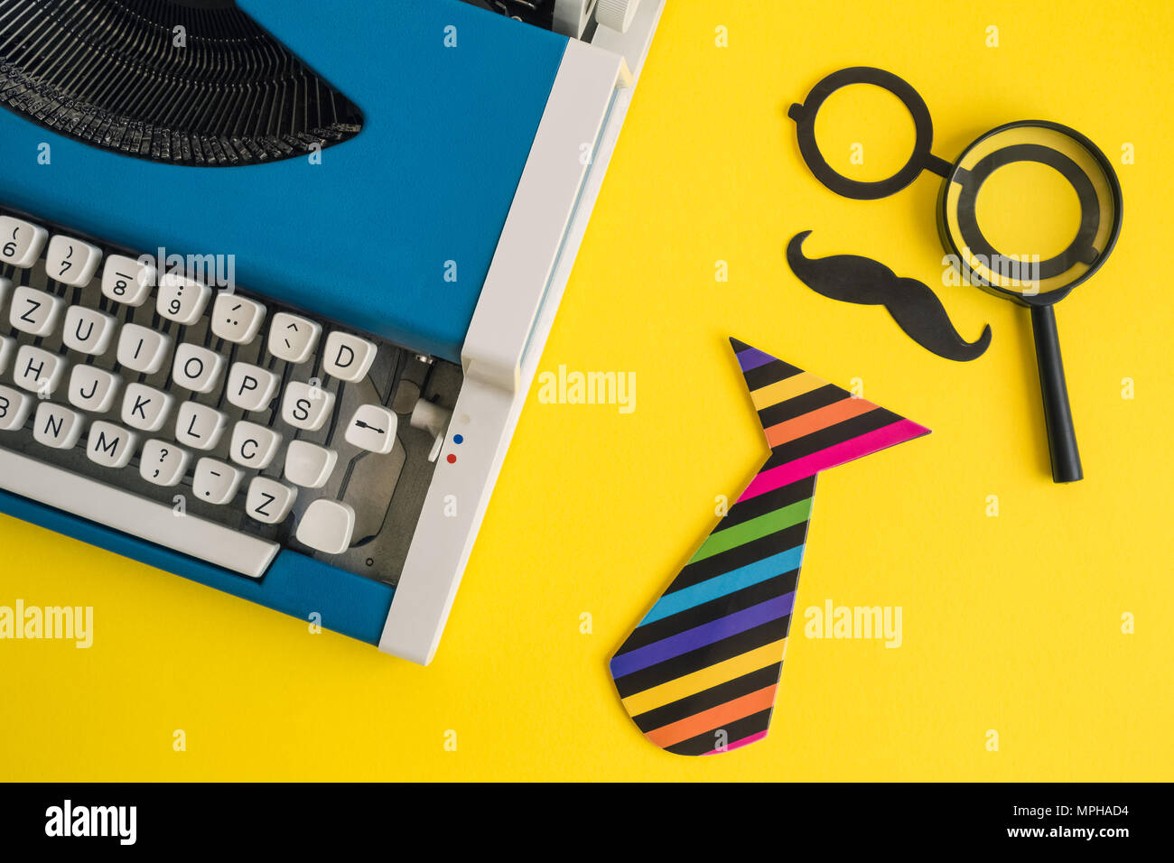 Flat Lay Of Vintage Blue Typewriter And Paper Props In Form Of Retro Hipster  Man With Magnifying Glass On Yellow Background Minimal Creative Concept.