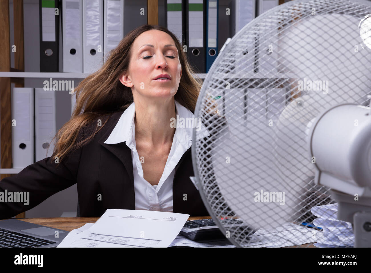 Mature Businesswoman Cooling Herself In Front Of Fan During Hot Weather - Stock Image
