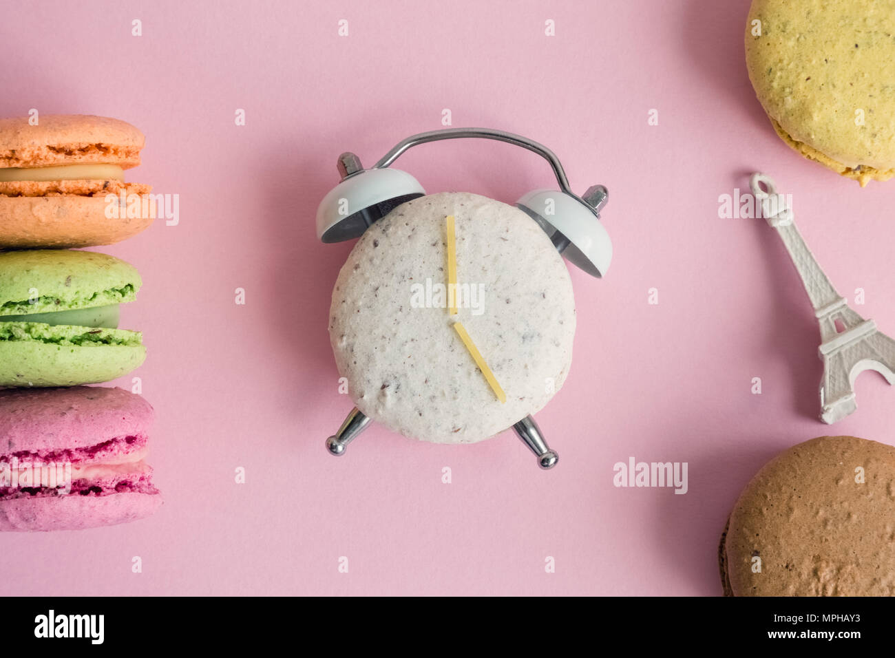 Flat lay of colorful macarons and Eiffel Tower miniature model on pastel pink background. One of macaroons in shape of alarm clock with clock hands ma Stock Photo