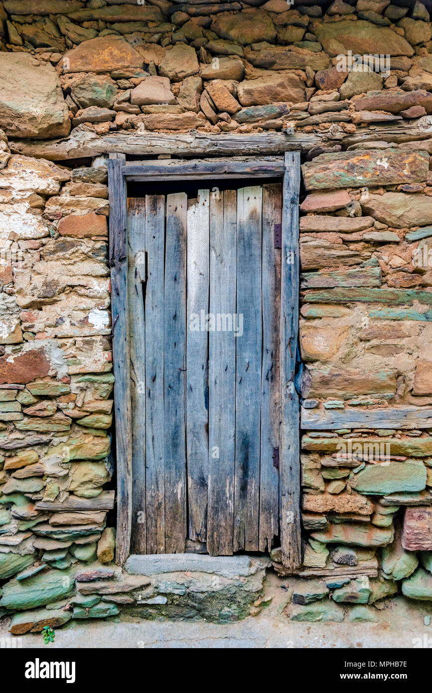 view of old rustic wooden door and big rocks wall for background