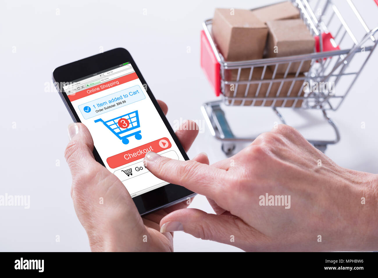 Close-up Of A Person Using Online Shopping Application On Mobile Phone With Cart - Stock Image