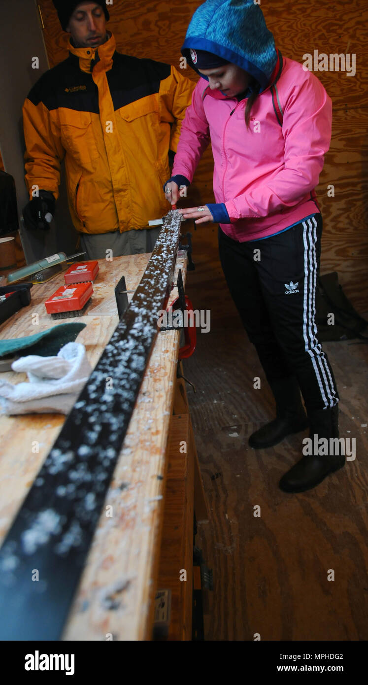 Pfc. Arica Carbaugh, a member of the Pennsylvania National Guard, waxes her skis in preparation for her next race at Camp Ethan Allen Training Site, Jericho, Vt., March 4, 2017. Over 120 athletes from 23 different states are participating in the 2017 National Guard Bureau Biathlon Championships. (Ohio National Guard photo by 1st Lt. Aaron Smith) - Stock Image