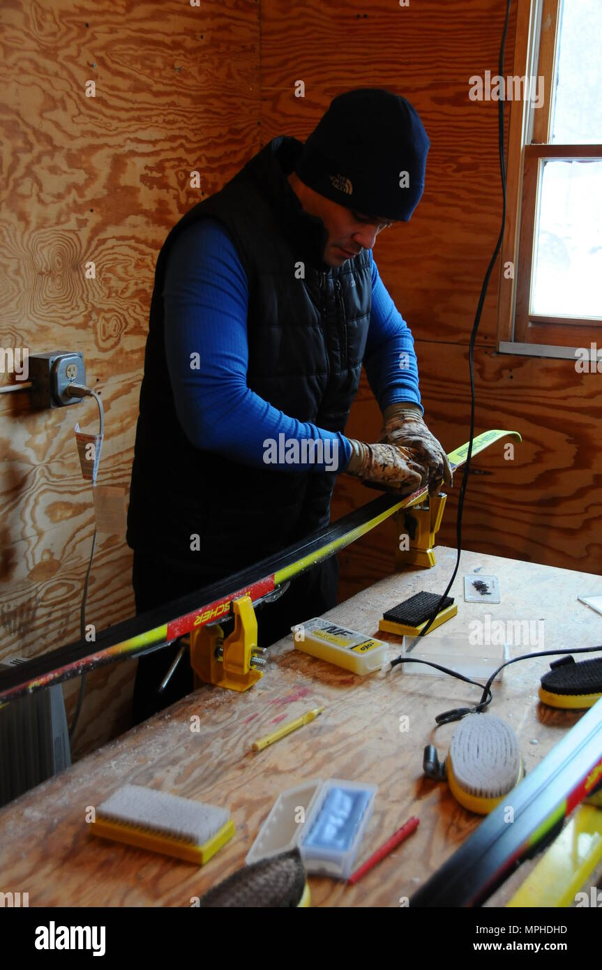 A U.S. Soldier, assigned to the Missouri National Guard, waxes his skis in preparation for his next race at Camp Ethan Allen Training Site, Jericho, Vt., March 4, 2017. Over 120 athletes from 23 different states are participating in the 2017 National Guard Bureau Biathlon Championships. (Ohio National Guard photo by 1st Lt. Aaron Smith) - Stock Image